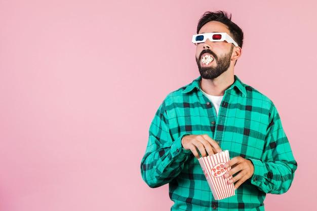 Medium geschoten kerel met mond vol popcorn