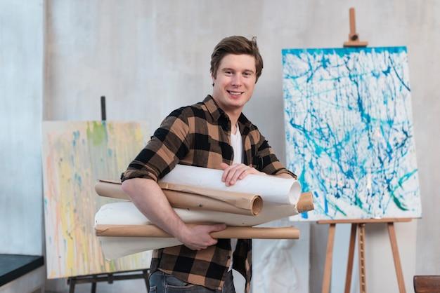Medium geschoten kunstzinnige man die zijn schilderijen vasthoudt