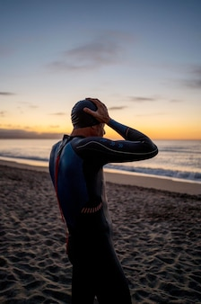 Medium geschoten man op strand bij zonsondergang