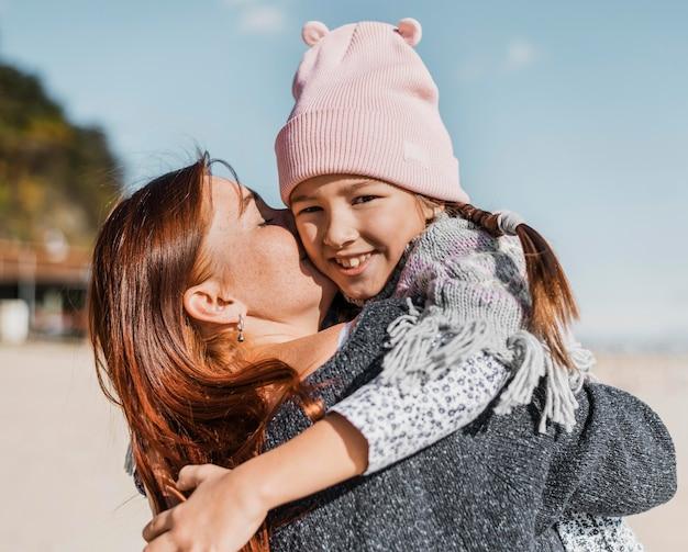 Medium geschoten moeder die klein meisje vasthoudt