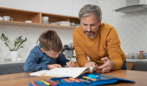 Medium geschoten vader die kind helpt met huiswerk Gratis Foto