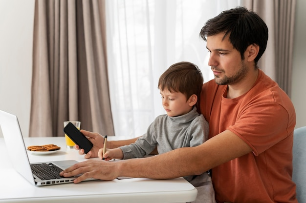Medium geschoten vader die op afstand met kind werkt