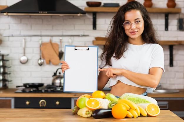 Medium geschotene smileyvrouw in de keuken