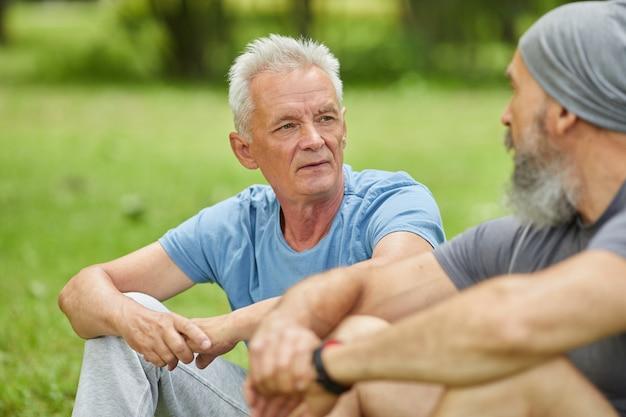 Medium portret van twee moderne senior mannen dragen casual outfits zittend op gras in park iets bespreken
