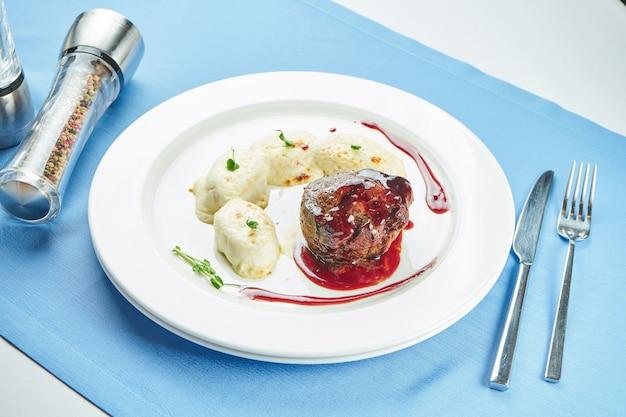 Medium rare filet mignon steak met bessensaus en aardappelgnocchi in een witte plaat op een blauw tafelkleed