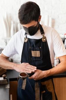 Medium shot barista met masker aan het werk
