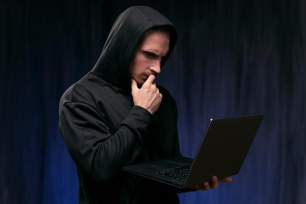 Medium shot bezorgde hacker met laptop
