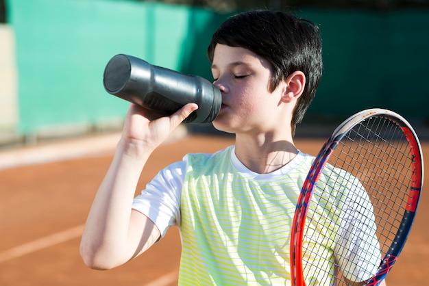 Medium shot brunette kid drinkwater met racket op de schouder