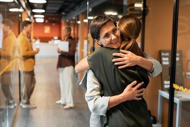 Medium shot collega's knuffelen op het werk