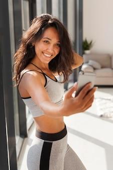 Medium shot fit vrouw selfie te nemen