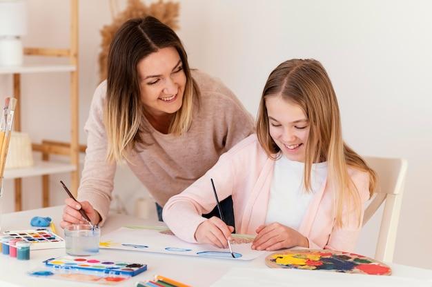 Medium shot gelukkig meisje en vrouw schilderen