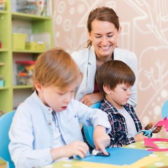Medium shot gelukkige leraar die naar kinderen kijkt