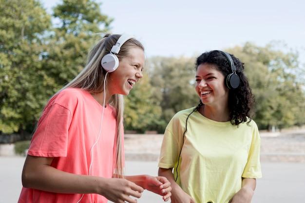 Medium shot gelukkige meisjes die naar muziek luisteren