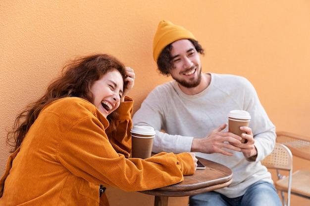Medium shot gelukkige vrienden met koffiekopjes