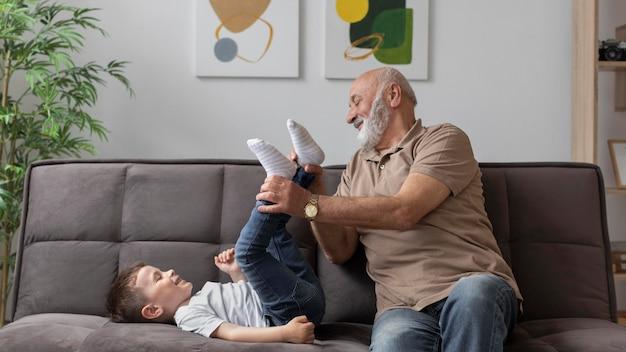 Medium shot grootvader speelt met jongen