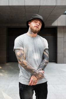 Medium shot jonge man met tatoeages en hoed Premium Foto