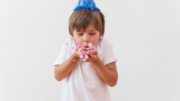 Medium shot jongen blaast roze bloemblaadjes