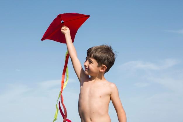 Medium shot jongen die met vlieger speelt Gratis Foto