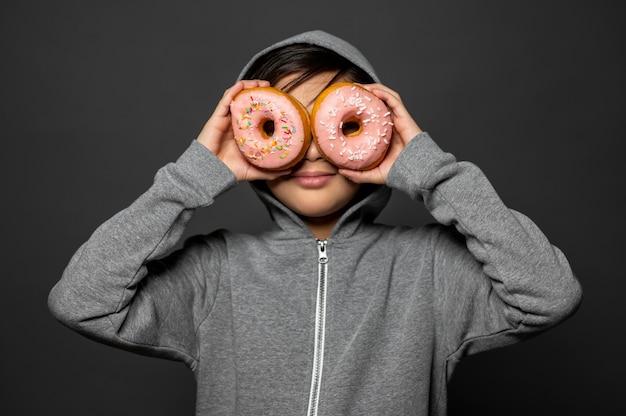Medium shot jongen met donuts