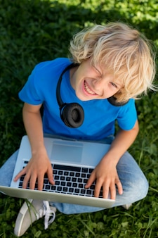 Medium shot jongen met laptop en koptelefoon