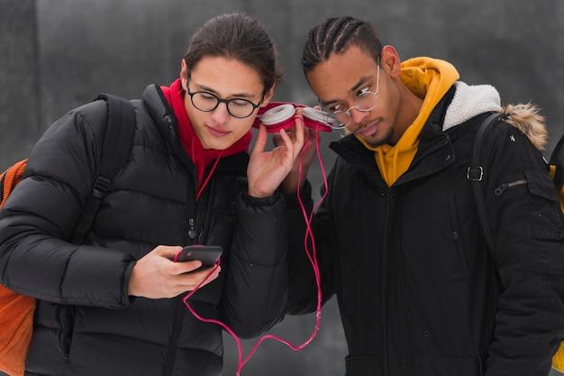 Medium shot jongens die buiten naar muziek luisteren