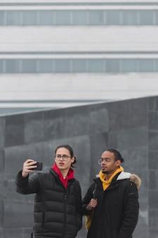Medium shot jongens die buitenshuis een selfie maken