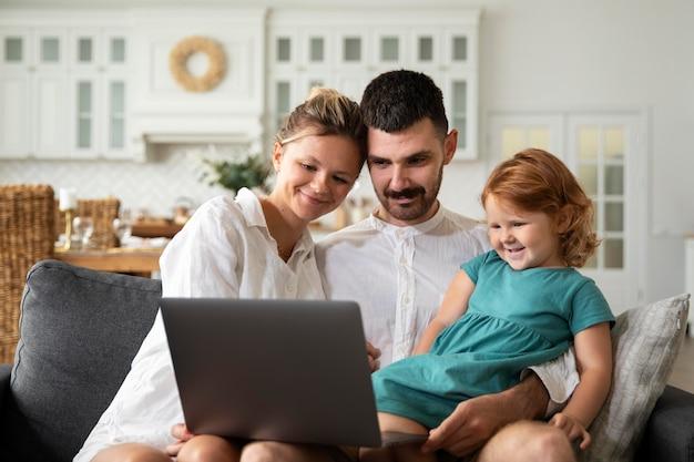 Medium shot kind en ouders met laptop