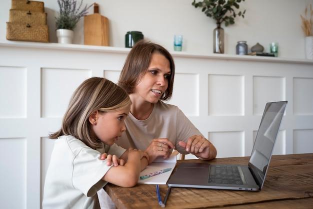 Medium shot kind en vrouw met laptop