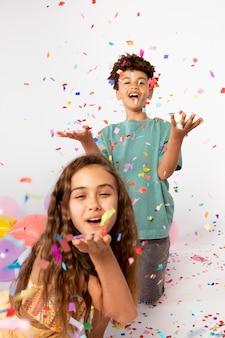 Medium shot kinderen die plezier hebben met confetti