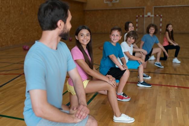 Medium shot kinderen die sporten in de sportschool