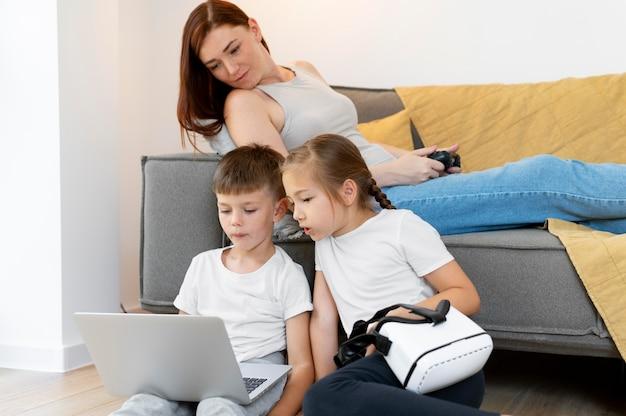 Medium shot kinderen en vrouw met apparaten