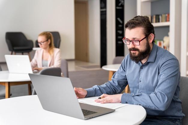 Medium shot man aan het werk met laptop