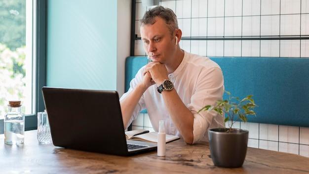 Medium shot man aan het werk op laptop