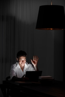 Medium shot man die 's nachts met apparaat werkt