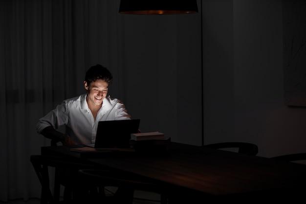 Medium shot man die 's nachts op laptop werkt