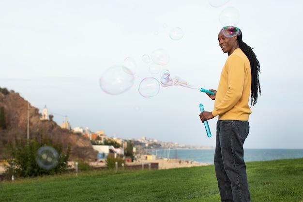 Medium shot man die zeepbellen maakt
