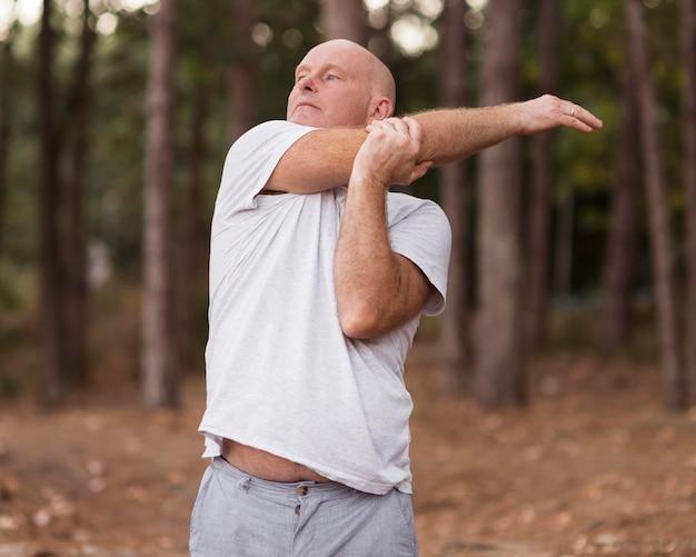 Medium shot man die zich uitstrekt in de natuur