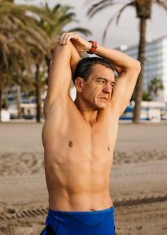Medium shot man die zich uitstrekt op het strand