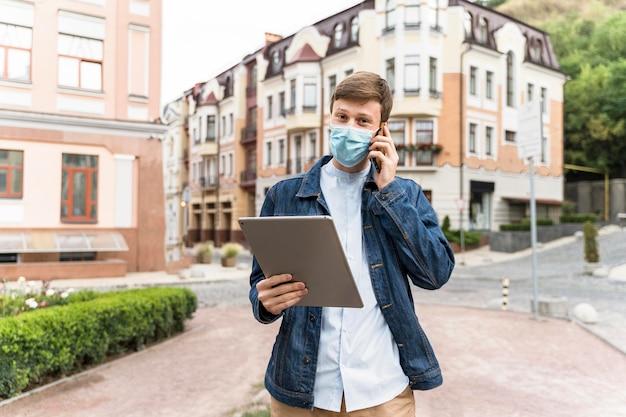 Medium shot man met een tablet terwijl hij een medisch masker draagt
