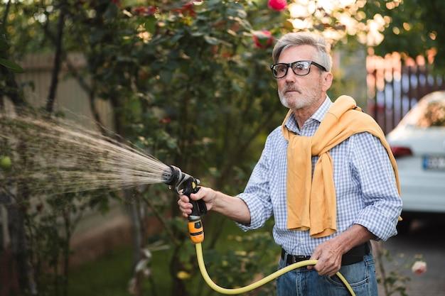 Medium shot man planten water geven