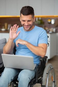 Medium shot man zwaaiend naar laptop