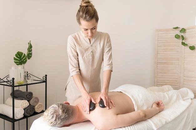 Medium shot masseuse met stenen