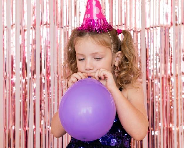 Medium shot meisje dat ballonnen opblaast