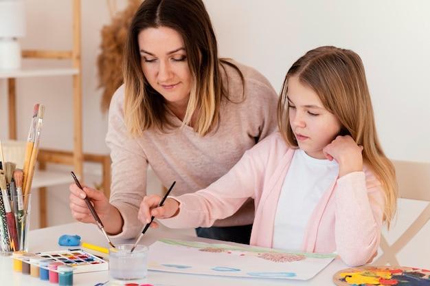 Medium shot meisje en vrouw schilderen