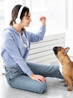 Medium shot meisje met hond traktatie