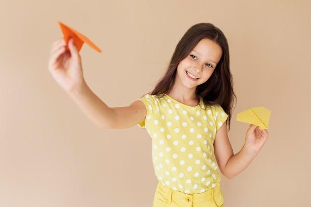 Medium shot meisje poseert met papieren vliegtuigjes