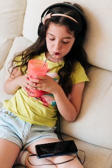 Medium shot meisje sap drinken en kijken naar telefoon