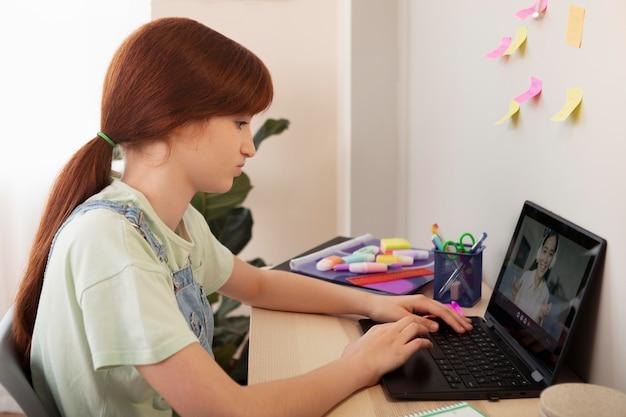 Medium shot meisje typt op toetsenbord