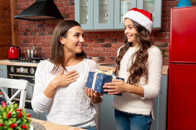 Medium shot meisje verrassende moeder met cadeau