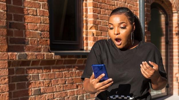 Medium shot meisje wordt geschokt terwijl ze naar haar telefoon kijkt